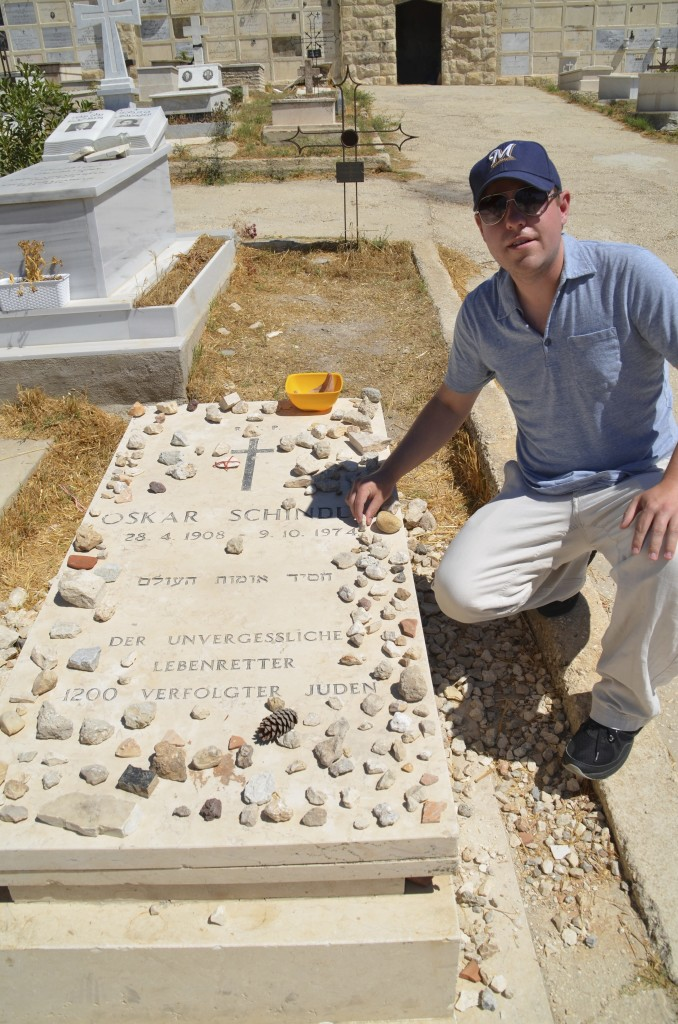 Placing a stone on the grave of Oskar Schindler at Mount Zion