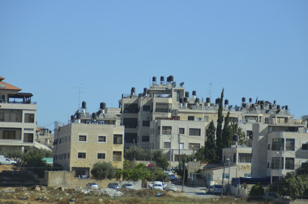 Black water containers on tops of Palestinian houses